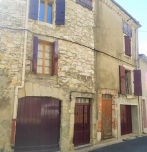 Maison de village de caractère à moderniser avec 135 m² habitables, 2 garages et terrasse.